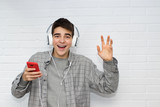 funny young man with mobile phone and earphones