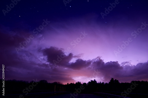 night sky with distant lightning storm and stars