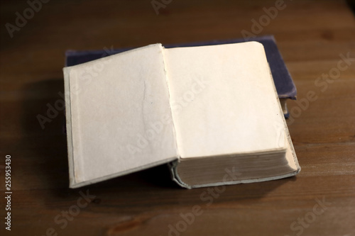 An open old retro book with white blank empty pages on which the designer can write a greeting text or a postcard on the wooden background of the library atmosphere