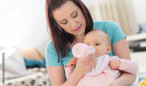 Leinwandbild Motiv Mother feeding baby girl with bottle