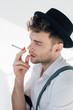 Leinwanddruck Bild - handsome man in white shirt and black hat smoking cigarette