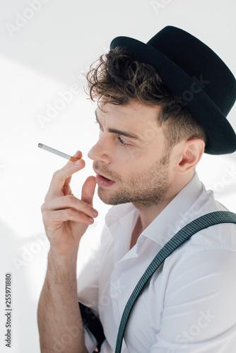 Leinwanddruck Bild handsome man in white shirt and black hat smoking cigarette