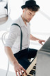 Leinwanddruck Bild - handsome pianist in white shirt and black hat playing piano