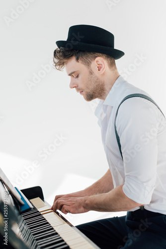 Leinwanddruck Bild concentrated pianist in stylish clothing playing piano