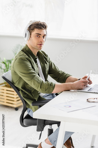 handsome businessman in headphones sitting at table with laptop, holding smartphone and listening music in office
