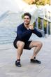 Leinwanddruck Bild - Smiling young sportsman doing squats
