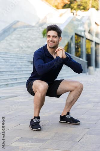 Leinwanddruck Bild Smiling young sportsman doing squats