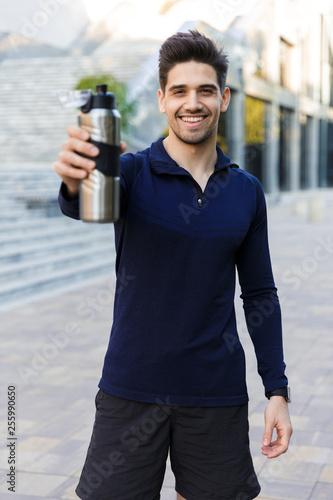 Leinwanddruck Bild Confident young sportsman holding water bottle