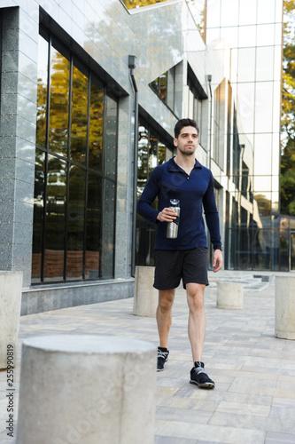 Leinwanddruck Bild Handsome young sportsman drinking water