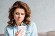 Leinwanddruck Bild - Beautiful curly woman in shirt sitting on sofa on grey