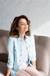 Leinwanddruck Bild - Blissful brunette woman in shirt sitting on sofa and smiling on grey