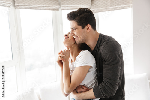 Portrait of caucasian couple laughing and hugging together while having fun at home