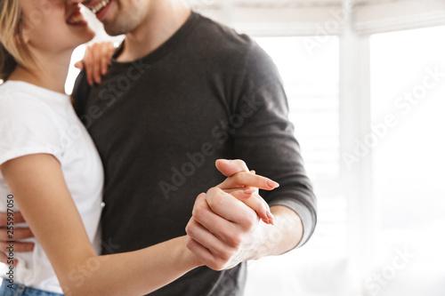 Leinwandbild Motiv Portrait of european couple hugging and dancing together while resting at home