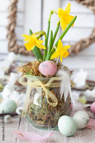 Leinwanddruck Bild Frische Osterglocken und bunte Eier