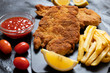 Traditional chicken schnitzel served with french fries, sauce and lemon. Black background. Close-up view - 256003628