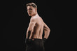back view of strong muscular mma fighter with hands on hips looking at camera isolated on black