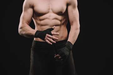 cropped view of strong shirtless muscular mma fighter fixing bandages isolated on black