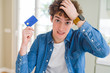 Young man holding credit card stressed with hand on head, shocked with shame and surprise face, angry and frustrated. Fear and upset for mistake.