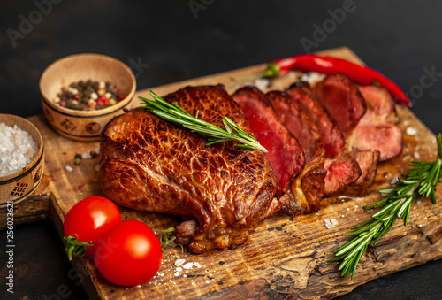 Beef steak, herbs and spices on a cutting board on a background of stone, top view - 256023621