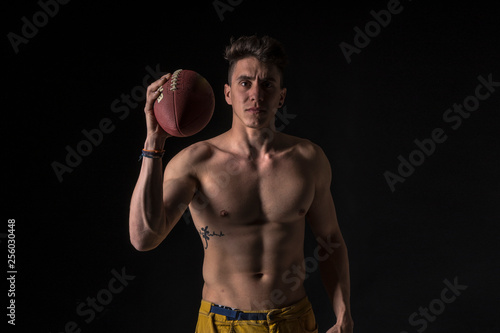american football player naked with abs on black background