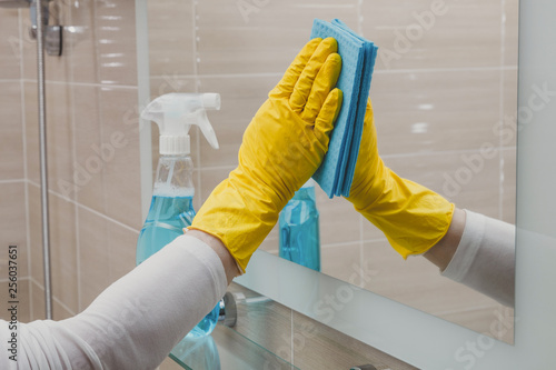 Leinwanddruck Bild Housemaid in the rubber gloves cleaning bathroom with a sponge