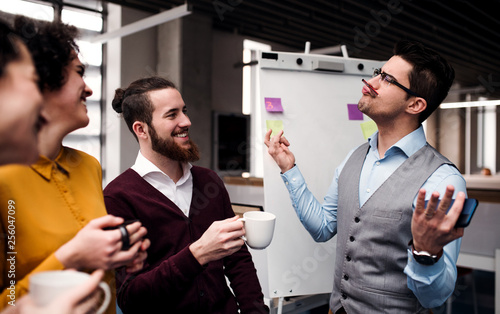 A group of young businesspeople with cup of coffee standing in office, having fun.