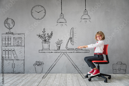 Happy child sitting at the desk in imaginary office © Sunny studio