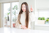 Beautiful Asian woman wearing casual sweater pointing finger up with successful idea. Exited and happy. Number one.