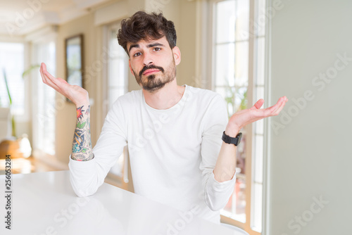 Leinwanddruck Bild Young man wearing casual shirt sitting on white table clueless and confused expression with arms and hands raised. Doubt concept.