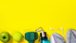 Leinwanddruck Bild - Fitness equipment and space for text on bright yellow background. Sport concept with sneakers, dumbbell, bottle of water, apple, tennis ball, headphones. Copy space, flat lay.Top view, banner.
