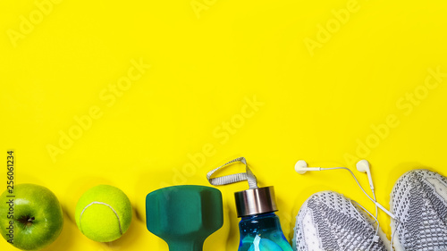Leinwanddruck Bild Fitness equipment and space for text on bright yellow background. Sport concept with sneakers, dumbbell, bottle of water, apple, tennis ball, headphones. Copy space, flat lay.Top view, banner.