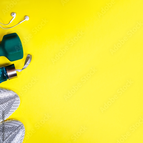 Leinwanddruck Bild Top view composition with fitness equipment and space for text on bright yellow background. Sport lifestyle concept with sneakers, dumbbell, bottle of water and headphones. Copy space, flat lay