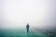 Male person walks alone on foggy field