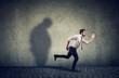 Leinwanddruck Bild - Man running away from his sad gloomy fat shadow on the wall.