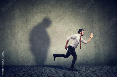 Leinwanddruck Bild Man running away from his sad gloomy fat shadow on the wall.