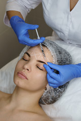 Aesthetic cosmetology. Facelift in spa salon. Beautician doing injection girl's brow creases. Smoothing facial wrinkles. Close-ups © Vagengeym