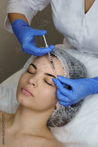 Leinwandbild Motiv Aesthetic cosmetology. Facelift in spa salon. Beautician doing injection girl's brow creases. Smoothing facial wrinkles. Close-ups