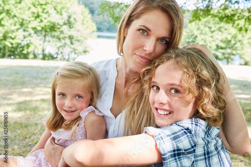 Glückliche Mutter umarmt ihre zwei Kinder