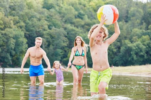 Leinwanddruck Bild Junge mit einem Ball spielt ausgelassen im Meer