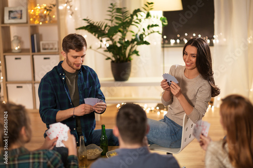 friendship, leisure and entertainment concept - happy friends with non-alcoholic beer playing cards game at home in evening