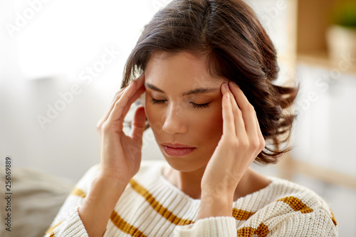 people , health and stress concept - unhappy woman suffering from head ache at home © Syda Productions