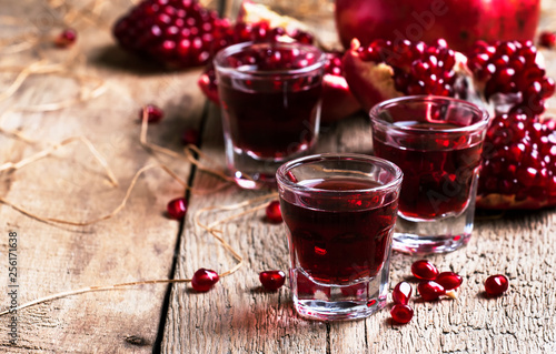 Homemade pomegranate liqueur, still life in rustic style, old wooden background, selective focus © 5ph