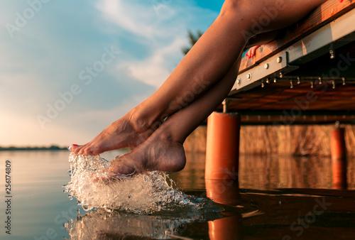 fototapeta na ścianę Woman legs as she sitting on wooden dock by the lake.