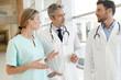 Leinwanddruck Bild - Doctors and nurse talking in hospital corridor