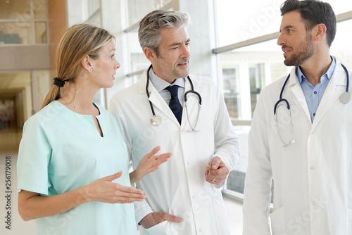Leinwanddruck Bild Doctors and nurse talking in hospital corridor