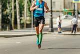 man runner in compression socks running marathon in hot weather
