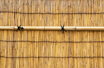 Yellow Bamboo cane wal with black knotsl as background © crisfotolux