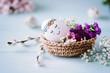 Leinwanddruck Bild - Schlafendes, süßes Osterei liegt im Osterkörbchen mit hübscher Blumendekoration