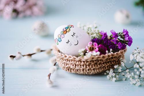 Schlafendes, süßes Osterei liegt im Osterkörbchen mit hübscher Blumendekoration - 256193888