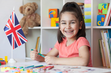 Happy smiling child girl lerning English